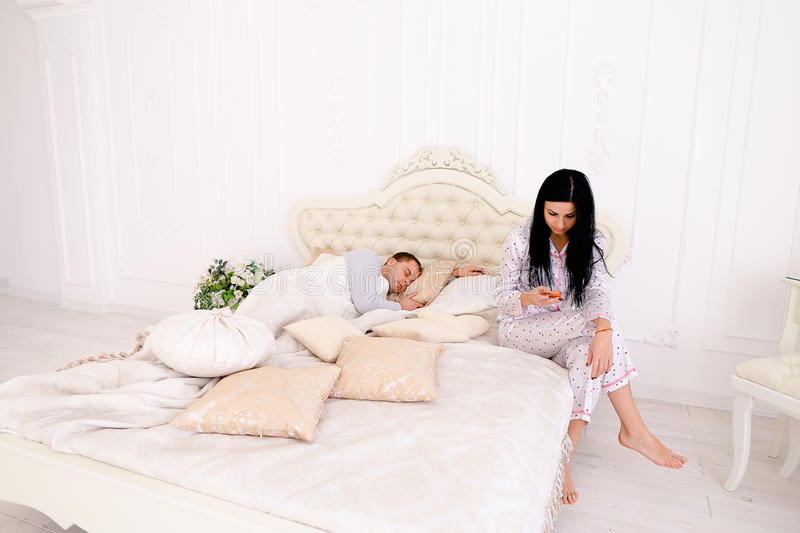 Wife checks meanly her husband`s phone, while he sleeps. Woman reading conversation while men sleeps. Female does not trust her boyfriend jealous. Couple stock photo