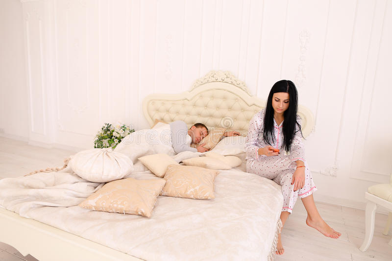 Wife checks meanly her husband`s phone, while he sleeps. Woman reading conversation while men sleeps. Female does not trust her boyfriend jealous. Couple stock photography