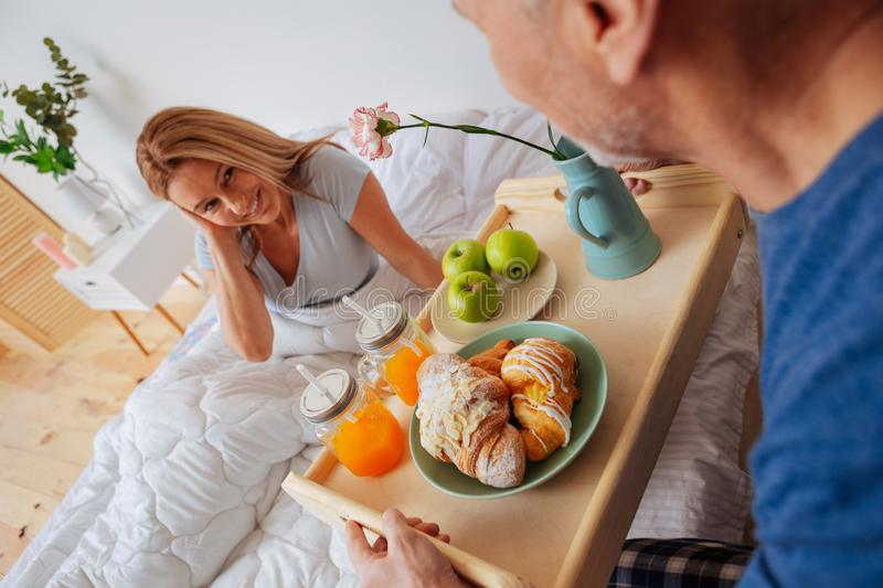 Wife feeling truly pleased seeing husband brining breakfast in bed royalty free stock photos