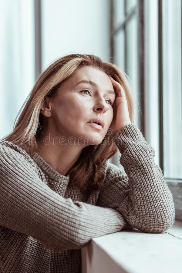 Wife feeling very stressed after quarrel with husband. Stressed after quarrel. Wife wearing brown sweater feeling very stressed after quarrel with husband stock photos