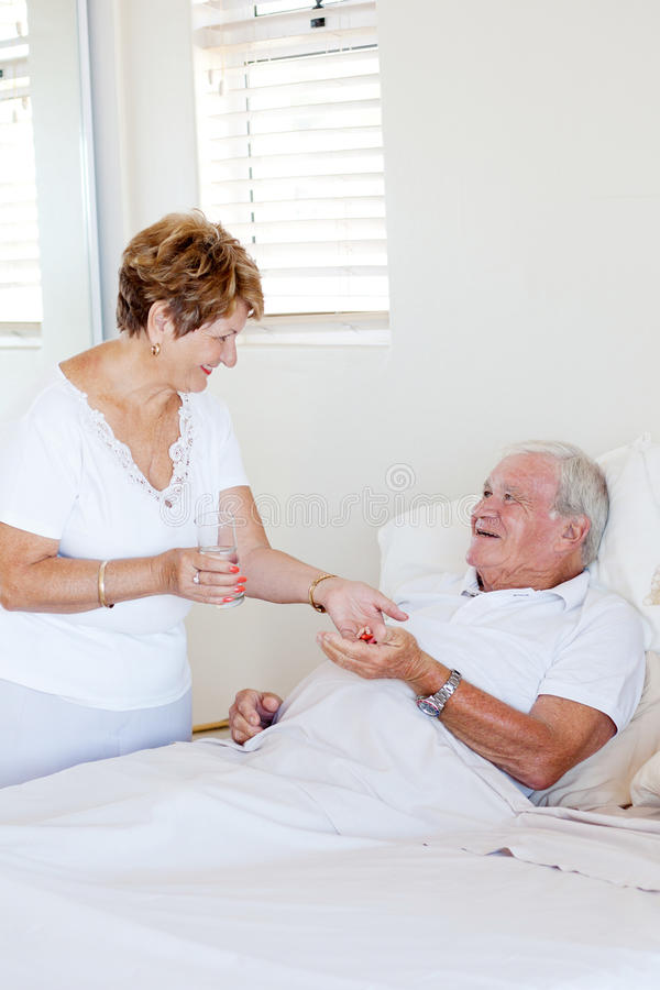 Wife giving medicine to husband royalty free stock image