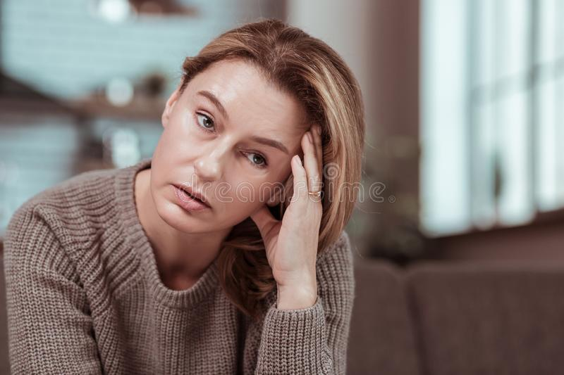 Wife having strong headache after big fight with husband. Strong headache. Blonde-haired stressed wife having strong headache after big fight with husband royalty free stock photos
