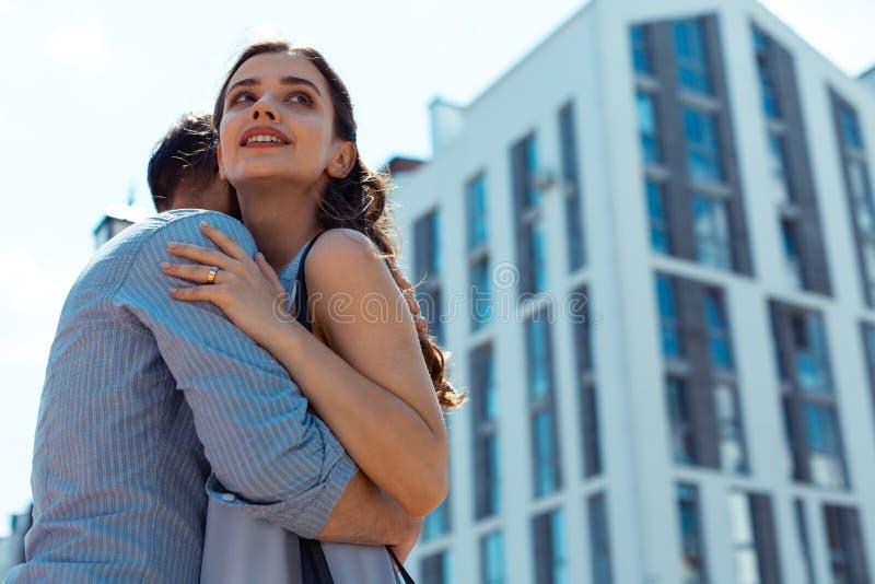 Dark-haired wife hugging her man wearing striped shirt. Wife hugging. Dark-haired loving young wife hugging her men wearing striped shirt stock photography