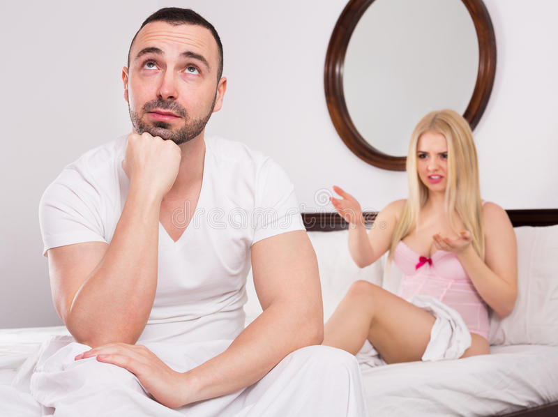 Wife and husband having difficulties in bed. Unsatisfied wife and sad young husband having big difficulties in the bed royalty free stock photos