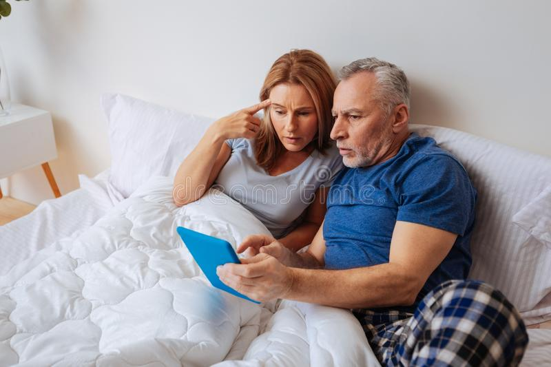 Wife and husband after reading political news on tablet royalty free stock photos