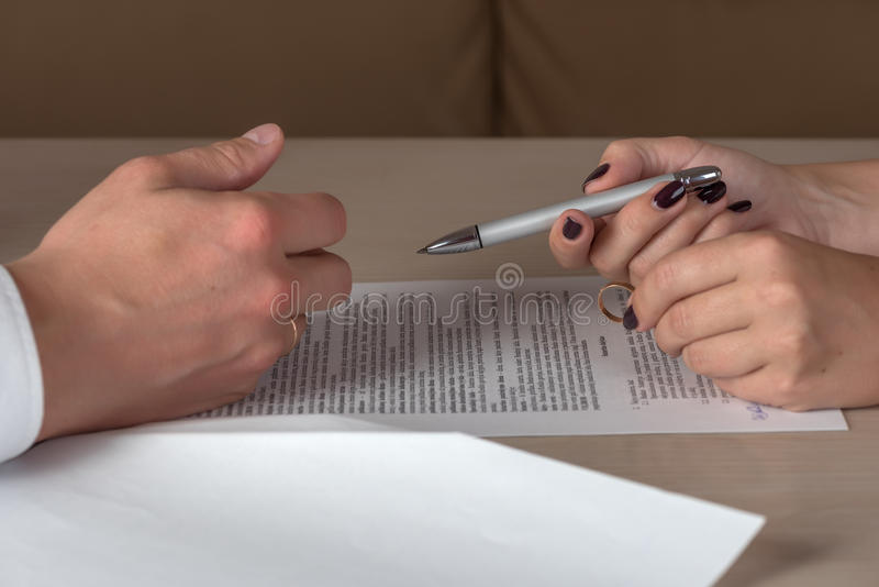 Wife and husband signing divorce documents, woman returning wedding ring stock photos