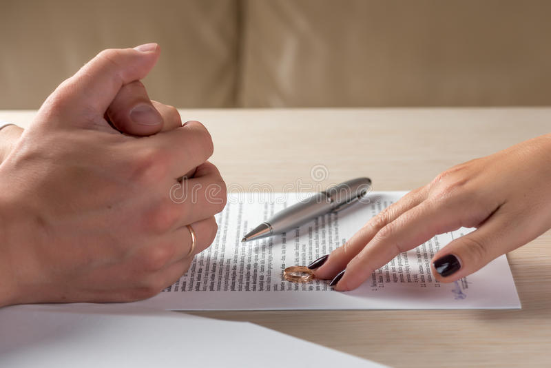 Wife and husband signing divorce documents, woman returning wedding ring royalty free stock photo