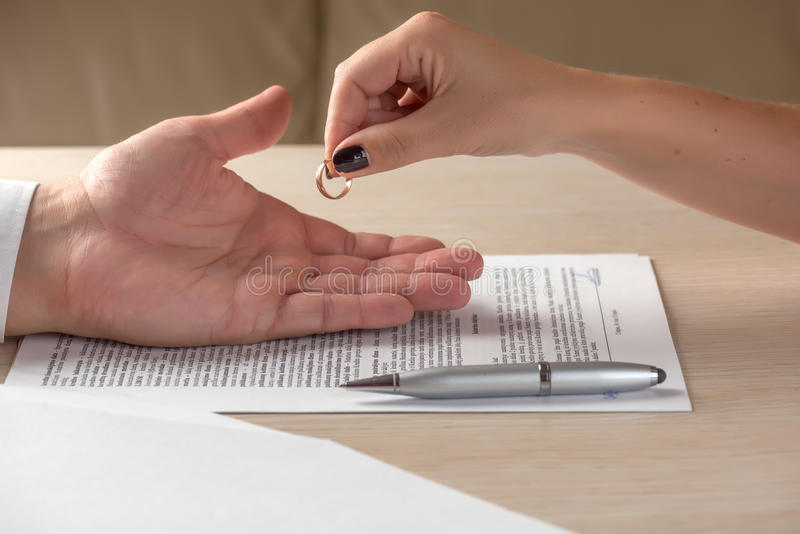 Wife and husband signing divorce documents, woman returning wedding ring royalty free stock photography