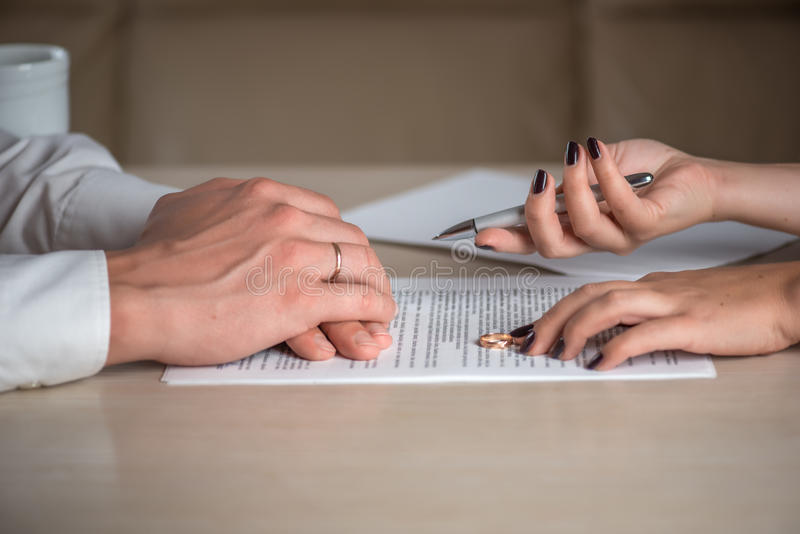 Wife and husband signing divorce documents, woman returning wedding ring stock images