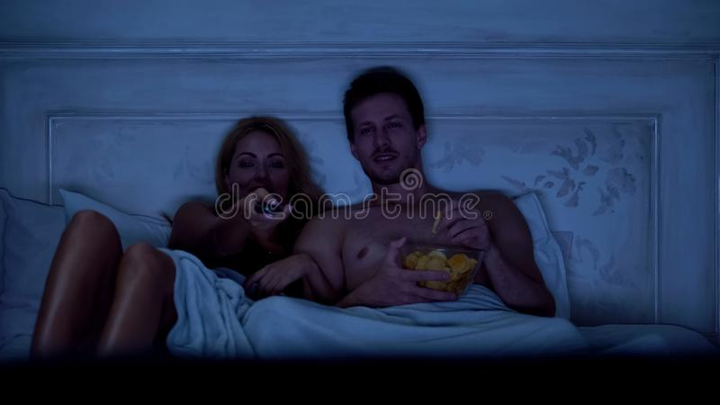 Wife and husband sitting in bed watching TV show, eating snacks and having fun royalty free stock image