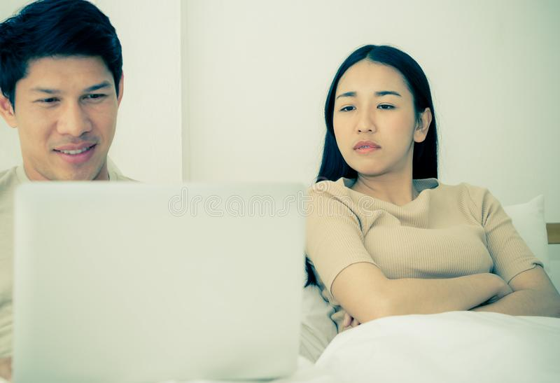 Wife on husband who go online social media. Angry wife on husband who go online social media stock photography