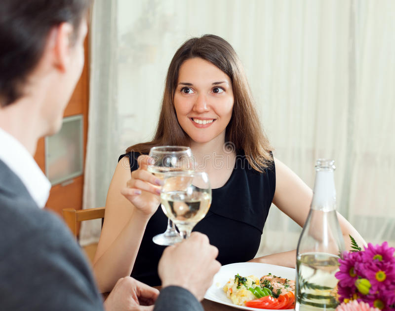 Wife with love looking at her husband and they together drinking. Champagne at dinner in home interior stock photography
