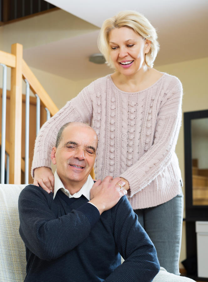 Wife massaging neck to husband stock photography