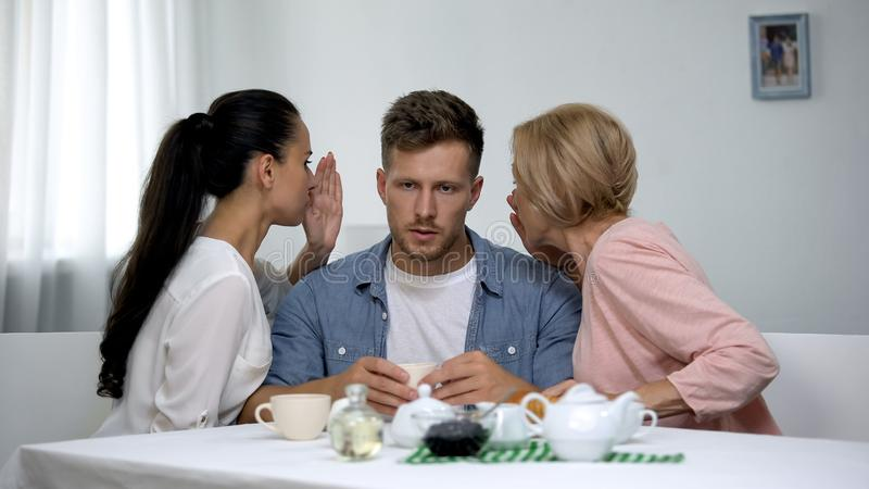 Wife and mother-in law in quarrel whispering man on ear, family confrontation. Wife and mother-in law in quarrel whispering men on ear, family confrontation royalty free stock photography