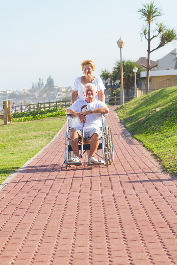Download Wife Pushing Husband On Wheelchair Stock Photo - Image: 14021680