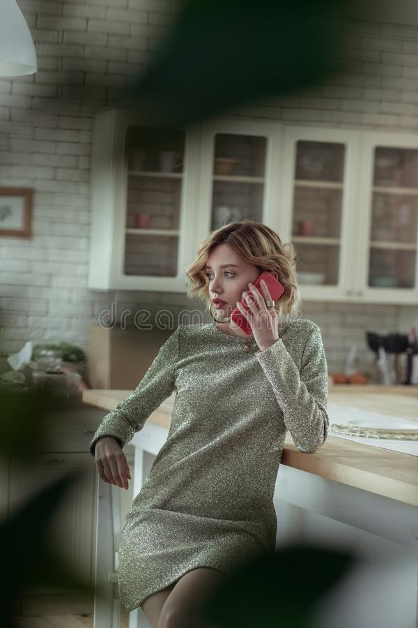 Wife with short hair cut calling husband feeling anxious. Calling husband. Curly wife with short hair cut calling her husband feeling anxious and worried stock photography
