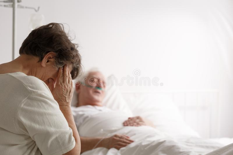 Wife sitting by dying husband. Depressed loving wife sitting by dying elderly husband in hospital stock photos