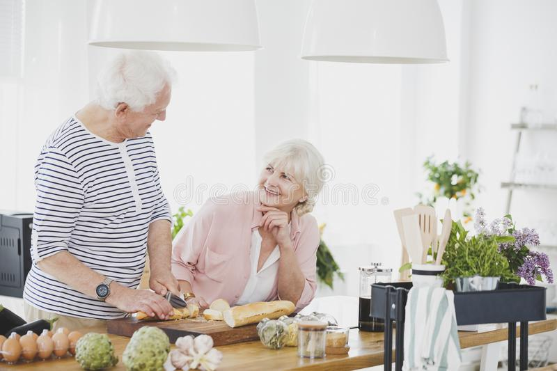 Wife smiling to elderly man. Elderly men cutting bread for breakfast while his wife smiling to him stock image