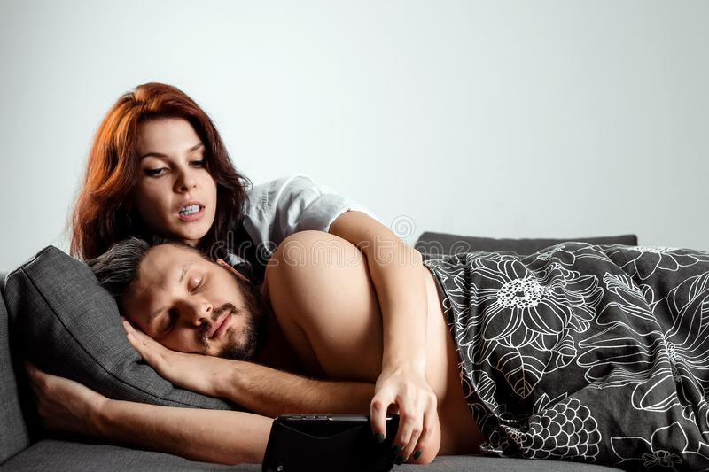The wife is spying on her husband`s phone while he sleeps. The concept of distrust, betrayal, jealousy, relationships, problems.  royalty free stock image