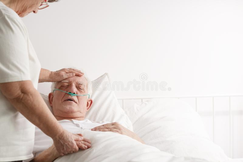 Wife supporting ill elderly husband royalty free stock image