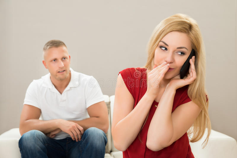 Wife Talking On Mobile Phone While Husband On Sofa Stock