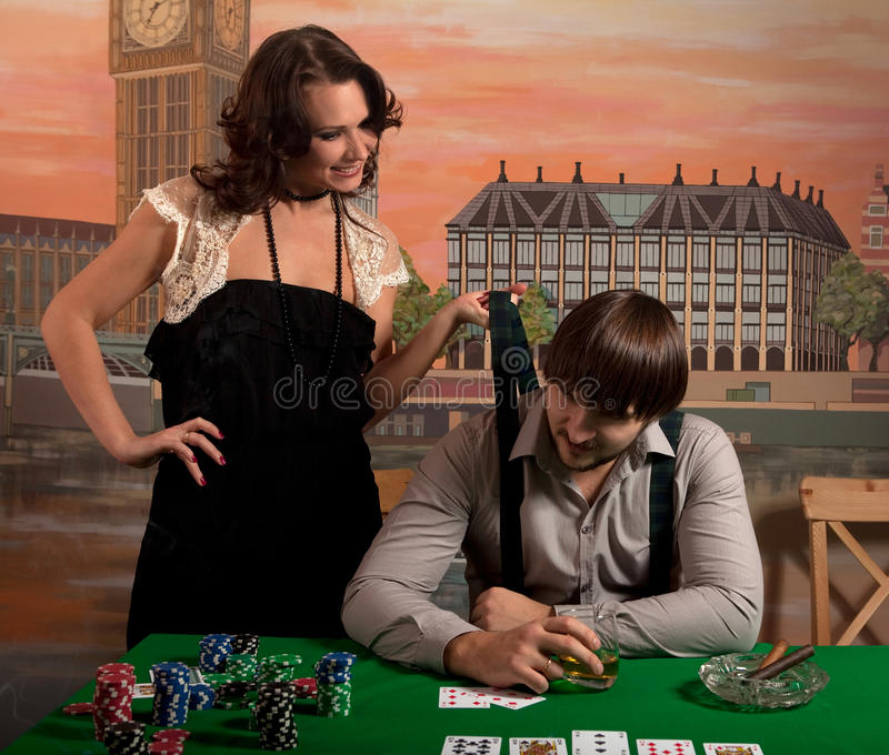 Wife tries to pull her husband from a poker game. royalty free stock photos