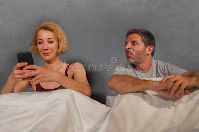 Wife using mobile phone in bed with her angry frustrated husband and the man feeling ignored upset and bored in woman internet add. Festyle portrait of royalty free stock photos