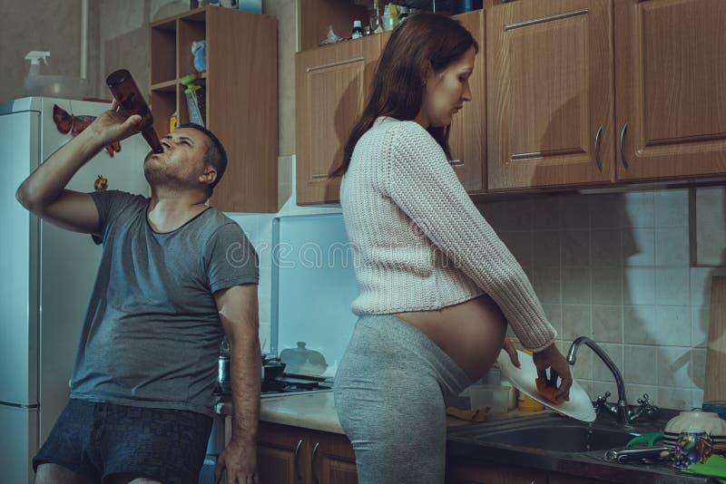 Wife washes the dishes, alcoholic husband. royalty free stock image