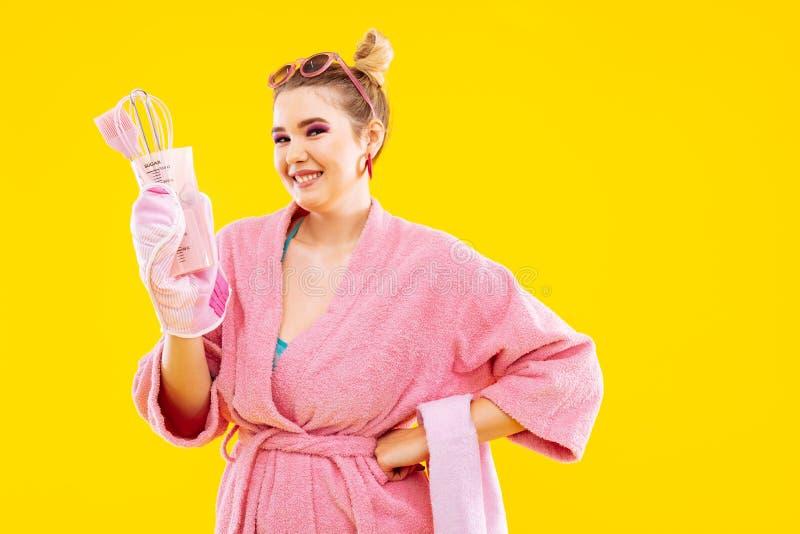 Wife wearing pink bathrobe smiling holding kitchen utensils. Kitchen utensils. Young beaming blonde wife wearing pink bathrobe smiling holding kitchen utensils royalty free stock image