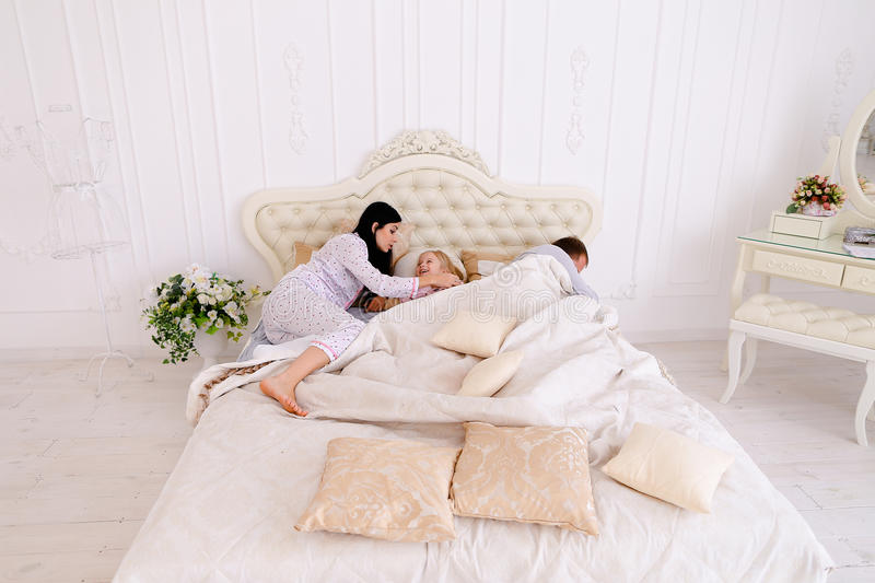 Wife yelling at daughter, husband sleeping on white bed in room royalty free stock image