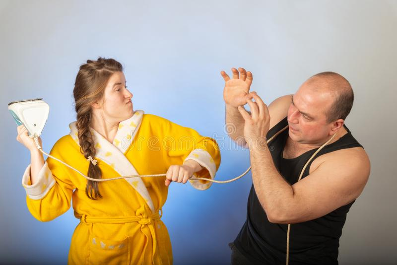 A wife in a yellow robe beats a bald husband, the concept of a family quarrel stock images