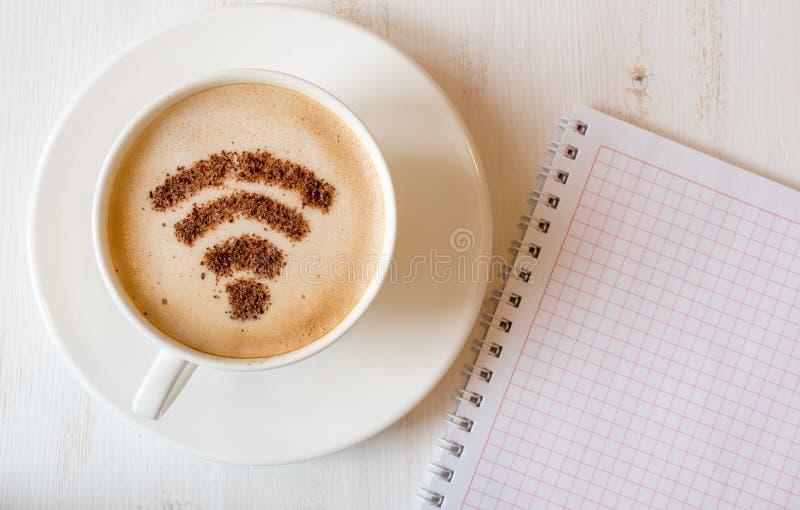 WiFi标志由桂香粉末制成当咖啡装饰在杯子热奶咖啡 免版税图库摄影