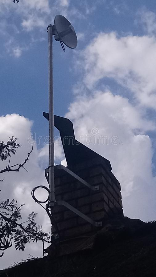 Wifi antena dołączał komin z wiatrowego vane sylwetką przeciw chmurnemu niebu zdjęcia royalty free