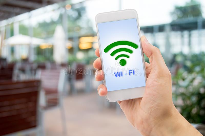 Wifi at the bar. Hand holding the smartphone searching the wifi signal at the terrace of bar royalty free stock photos