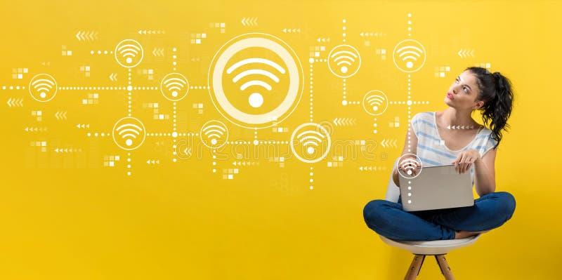 Wifi begrepp med kvinnan som använder en bärbar dator arkivbild