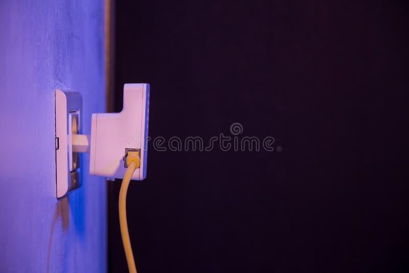 WiFi extender i elektrisk hålighet på väggen med Ethernettaxin fotografering för bildbyråer