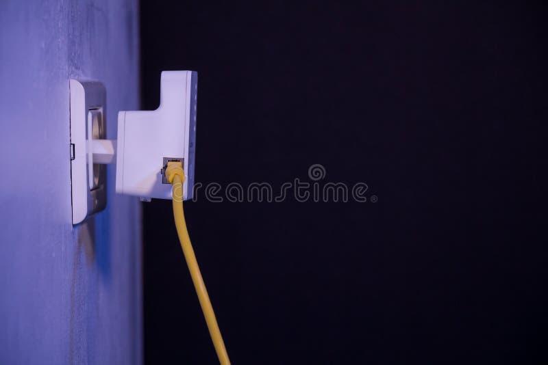 WiFi extender i elektrisk hålighet på väggen med Ethernettaxin arkivfoton