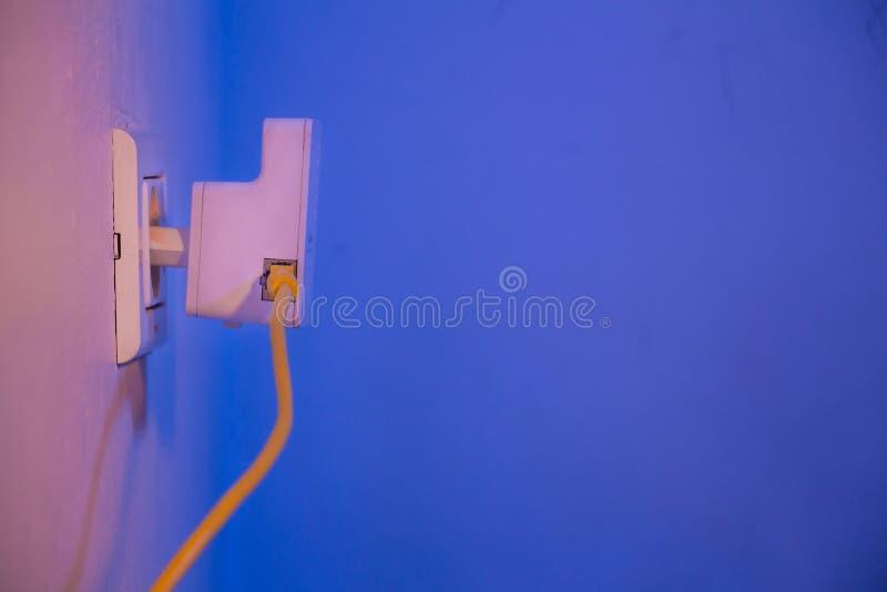 WiFi extender i elektrisk hålighet på väggen med Ethernettaxin arkivbild