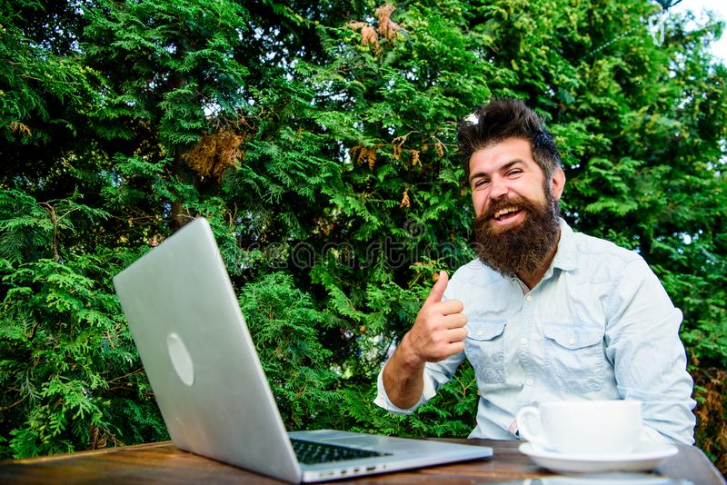 Wifi and laptop. Drink coffee and work faster. Bearded man successful freelance worker. Remote job. Freelance. Professional occupation. Good job expression stock photography