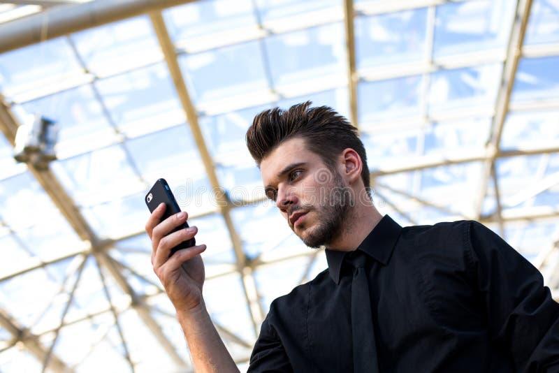 Wifi masculino hermoso de la ojeada del gestor de proyecto vía el teléfono de célula, colocándose en terminal de aeropuerto fotos de archivo libres de regalías