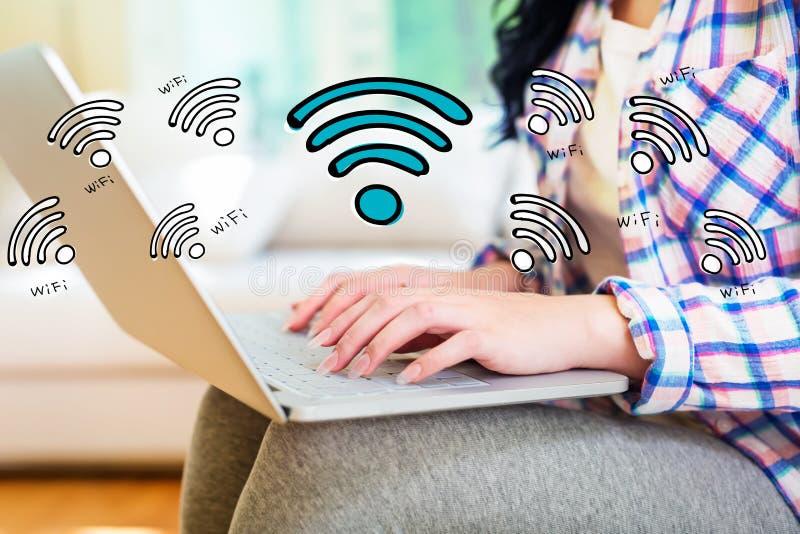 WiFi med kvinnan som använder en bärbar dator royaltyfri bild