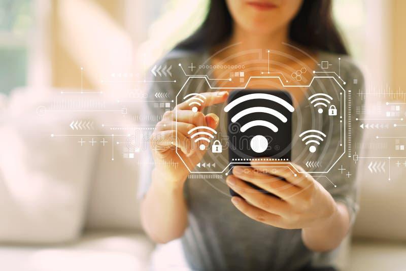 Wifi med kvinnan som använder en smartphone royaltyfri bild