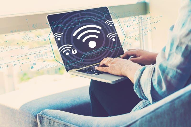 WiFi med kvinnan som anv?nder b?rbara datorn royaltyfri bild