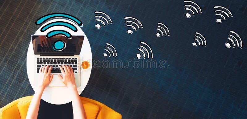 WiFi med personen som använder en bärbar dator arkivbilder
