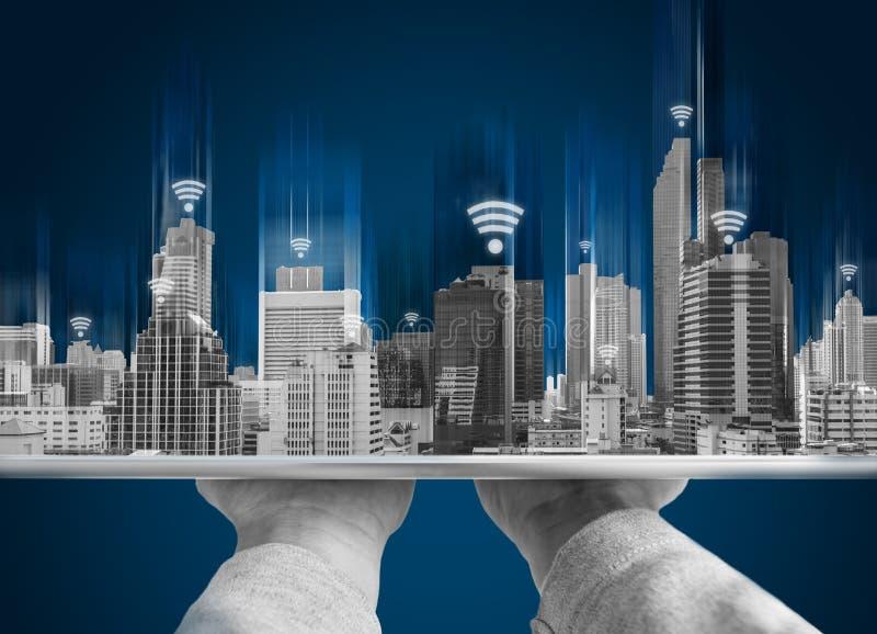 Wifi nätverksanslutning och smart stadsbegrepp Räcka det hållande digitala minnestavla- och byggnadshologrammet med wifisignaltec royaltyfri foto