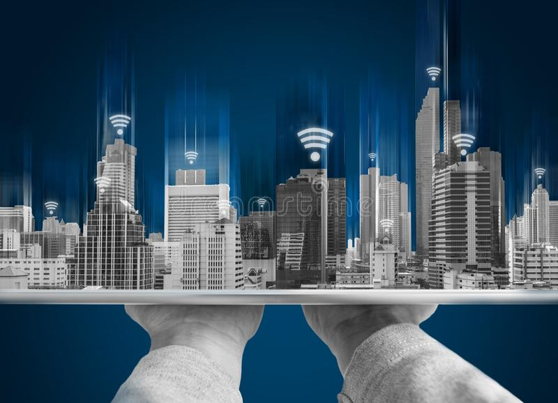 Wifi network connection and smart city concept. Hand holding digital tablet and building hologram with wifi signal sign. S royalty free stock photo