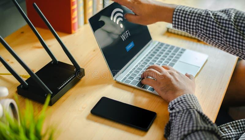 Wifi se reliant de routeur de jeune homme sur le smartphone pour l'Internet et les médias sociaux images libres de droits