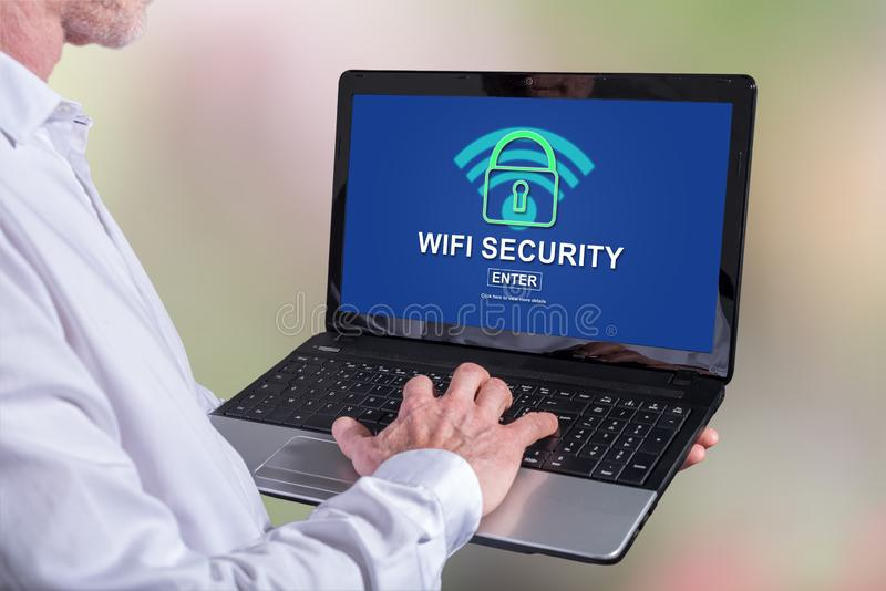 Wifi security concept on a laptop. Man using a laptop with wifi security concept on the screen stock image