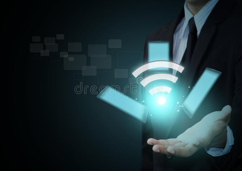 Wifi symbol and touch pad technology. On businessman hand
