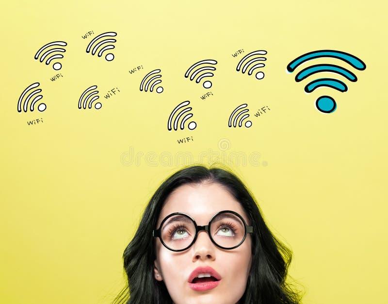 WiFi tema med den unga kvinnan arkivbilder